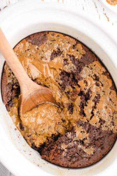 close up overhead shot of crockpot chocolate caramel cake in a crockpot being picked up with a wooden spoon
