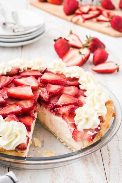 strawberry cream cheese pie with sliced strawberries and a whipped topping in a clear pie dish