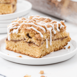 side shot of a slice of coffee cake on a white plate