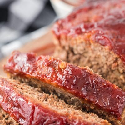 A close up of a piece of cake on a paper plate, with Meatloaf