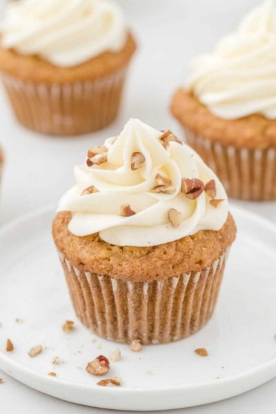 carrot cake cupcakes with cream cheese frosting and sprinkled with chopped walnuts on a white plate