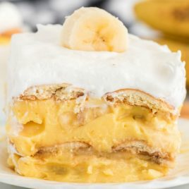 A close up of a doughnut on a plate, with Banana and Pudding