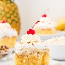 a slice of Hawaiian wedding cake topped with walnuts, cool whip, and a cherry on a plate