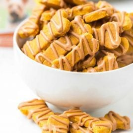 close up shot of Pumpkin Dog Treats drizzled with peanut butter and piled in a bowl