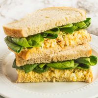 two egg salad sandwiches stacked on a plate