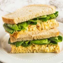 A sandwich cut in half on a plate, with Egg salad
