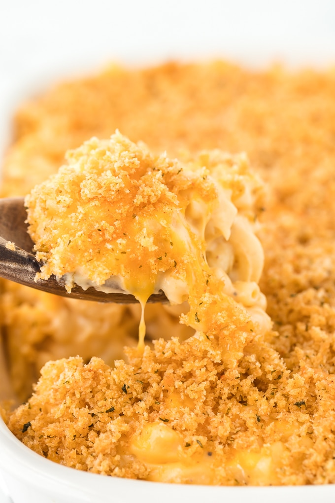 wooden spoon lifting spoonful of baked mac and cheese out of casserole dish
