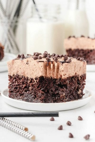 chocolate poke cake garnished with chocolate chips on a white plate