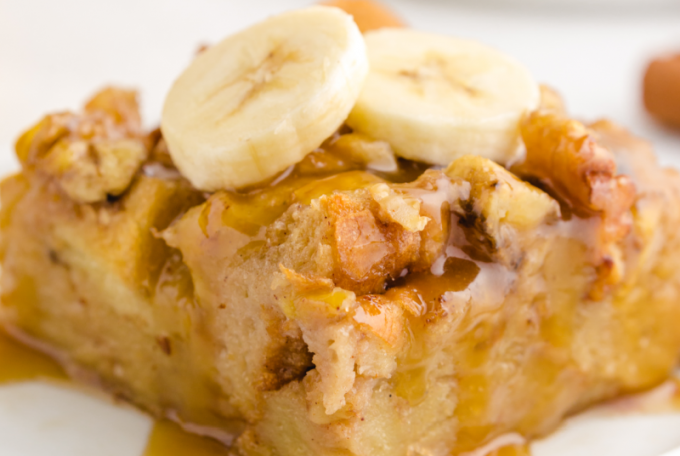 close up shot of banana bread pudding with banana slices on top on a white plate