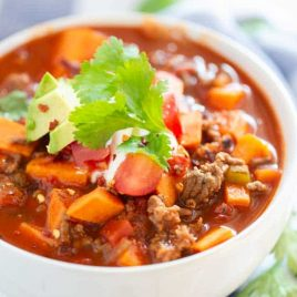 A bowl of food on a plate, with Sweet potato
