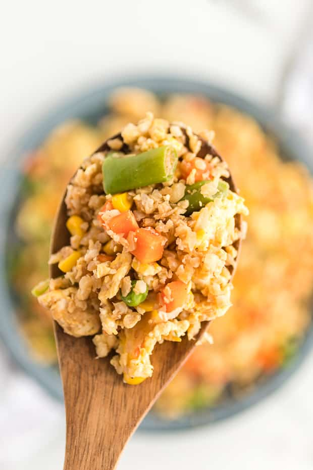 wooden spoon full of fried cauliflower rice