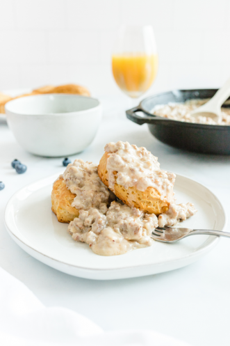 country biscuits and sausage gravy on a white plate