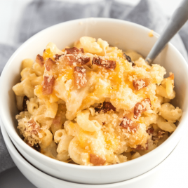 A bowl of food on a plate, with Bacon and Cheese