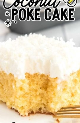 close up shot of coconut poke cake with coconut frosting on a white plate with a piece taken out of it with a fork