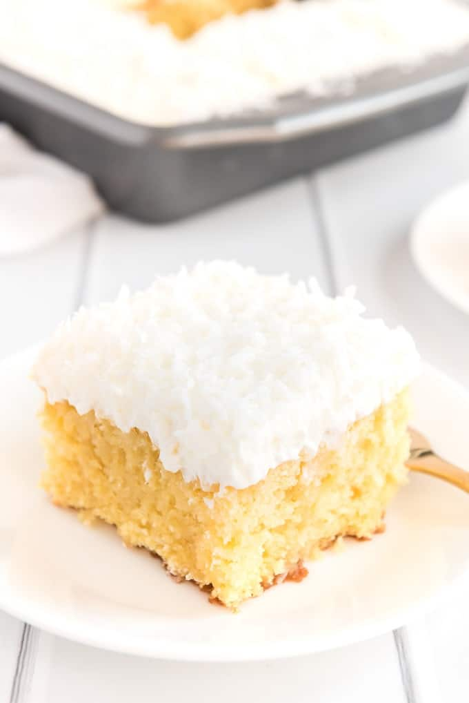 A piece of cake on a plate, with Coconut and Cream