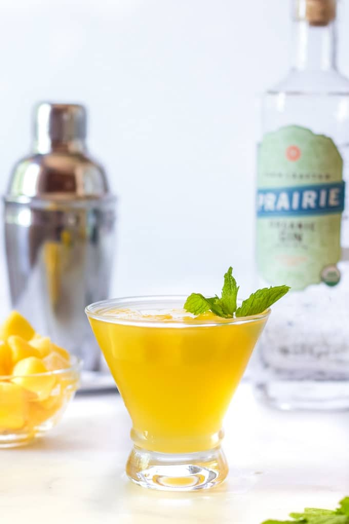 A bottle of wine and a glass of orange juice, with Mojito recipe
