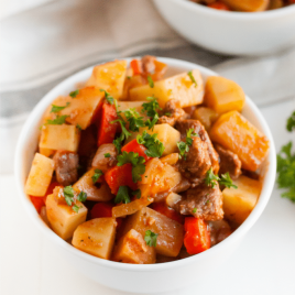A bowl of food on a plate, with Beef and Stew