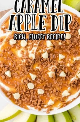 close up overhead shot of a bowl of caramel apple dip topped with caramel, toffee, and white chocolate with sliced apples on the side for dipping