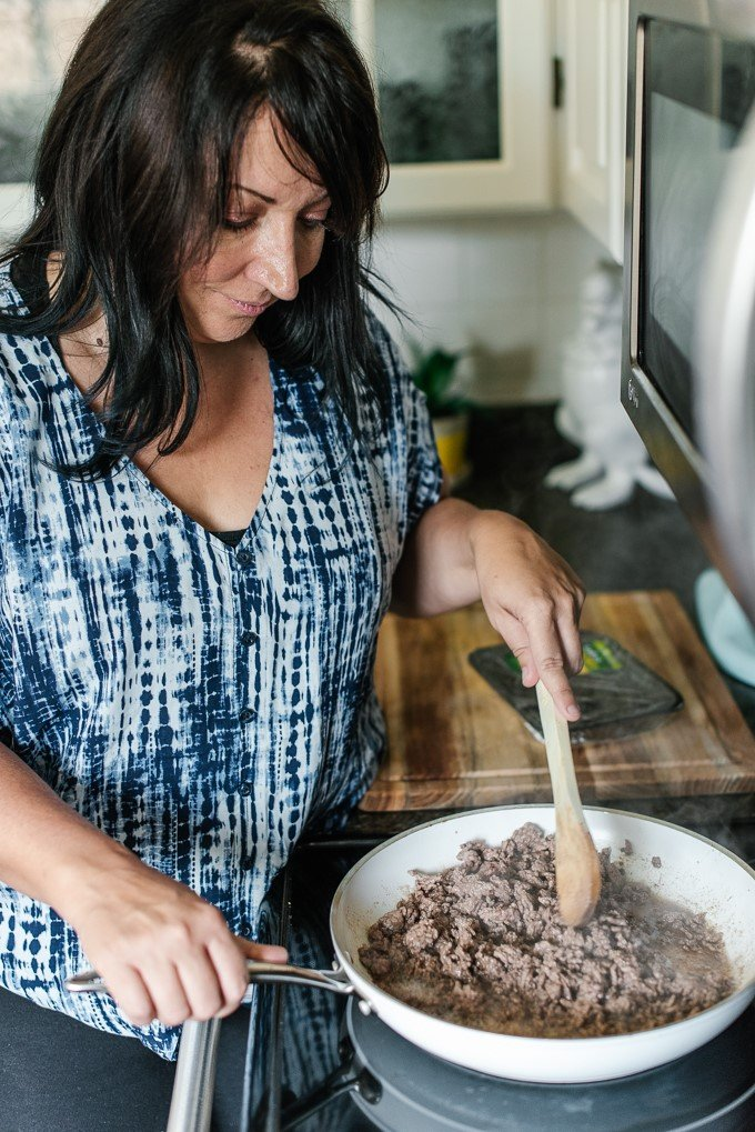 A woman preparing food in a bowl, with Ground beef