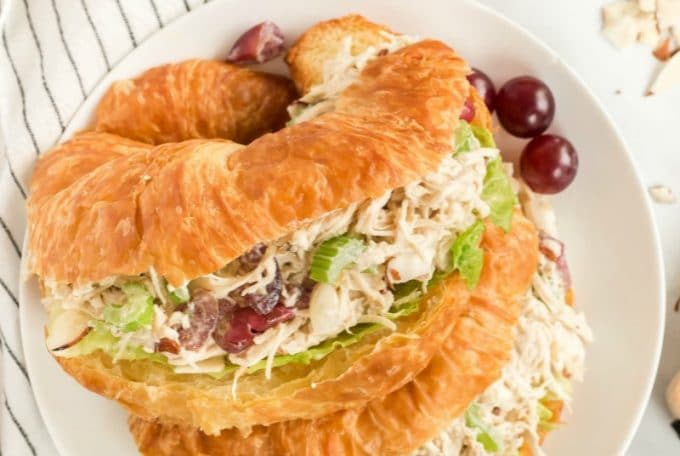 chicken salad sandwich on a plate with grapes