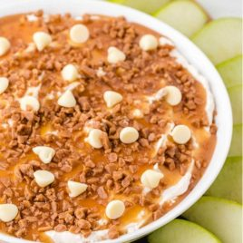 close up shot of a bowl of caramel apple dip topped with caramel, toffee, and white chocolate with sliced apples on the side for dipping