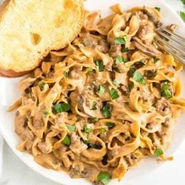 close up overhead shot of a serving of Ground Beef Stroganoff topped with parsley and served with a piece of bread