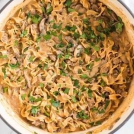 close up overhead shot of Ground Beef Stroganoff topped with parsley in a pot