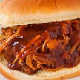 close up shot of a Instant Pot Pulled Pork sandwich with bbq sauce on a plate