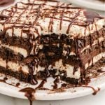 close up shot of icebox cake drizzled with chocolate syrup on a white plate