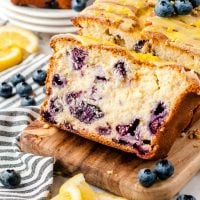 A piece of cake sitting on top of a wooden cutting board, with Blueberry and Bread