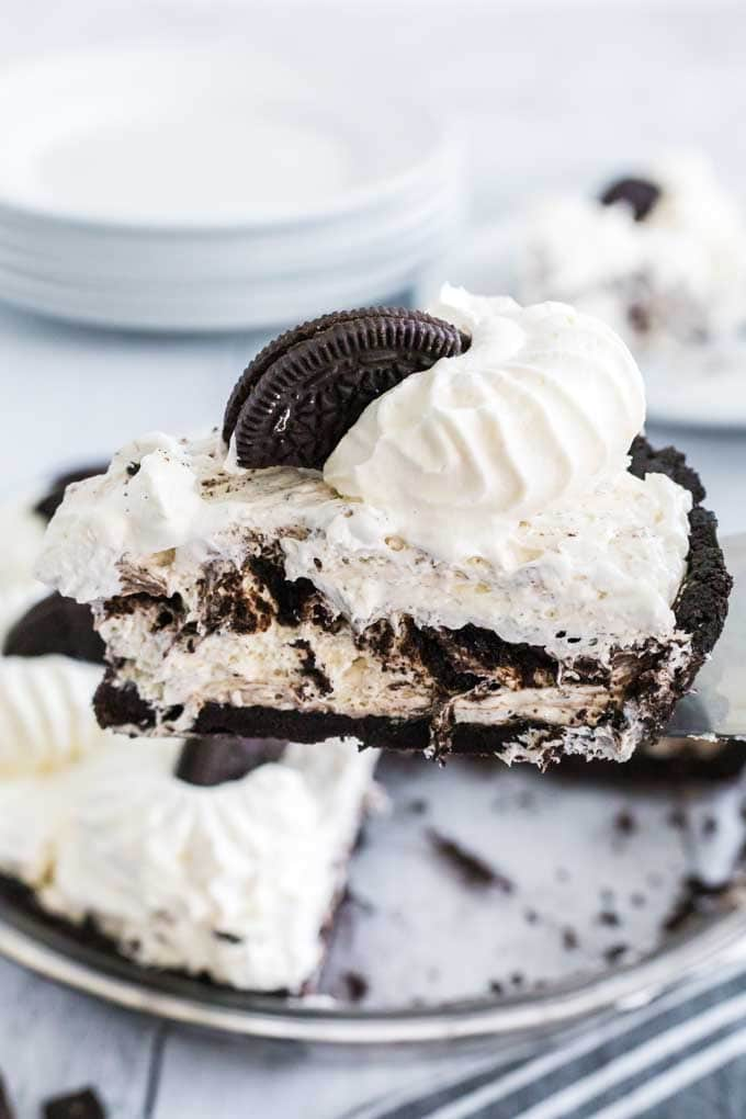 A piece of cake and ice cream on a plate, with Oreo and Cookie