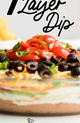 close up shot of a bowl of seven layer dip topped with sliced tomatoes, green onions, and black olives