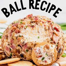 close up shot of cheese ball recipe with cheese being spread onto ritz cracker