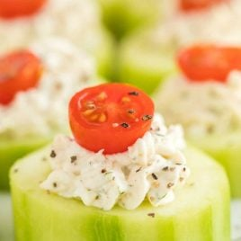 close up shot of Cucumber Bites topped with cream cheese and a slice of grape tomato