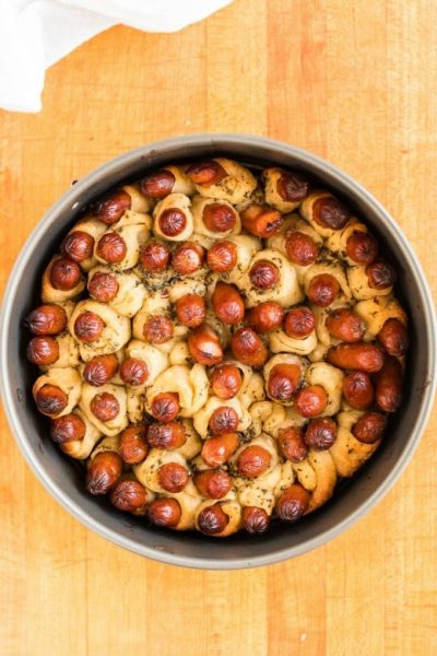 A bowl of fruit sitting on top of a wooden table, with Pigs in a blanket
