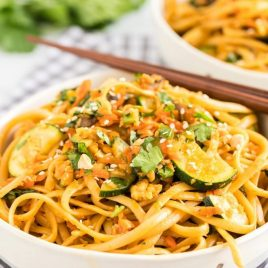 A bowl of pasta sits on a plate, with Noodle