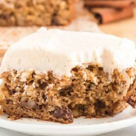 close up shot of a slice of Applesauce Cake topped with cream cheese frosting on a plate with a fork