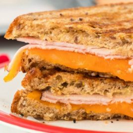 A close up of a sandwich on a plate, with Cheese and Ham