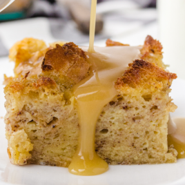 close up shot of bread pudding on a white plate with glaze being poured on it