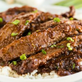 A close up of a plate of food with meat and vegetables, with Mongolian beef