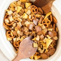 chex mix in a slow cooker being stirred with wooden spoons