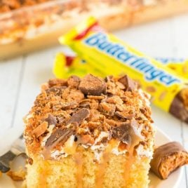 A plate of food with a slice of cake on a table, with Butterfinger