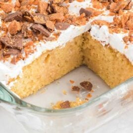 close up shot of Butterfinger Cake garnished with butterfinger candy bits in a baking dish