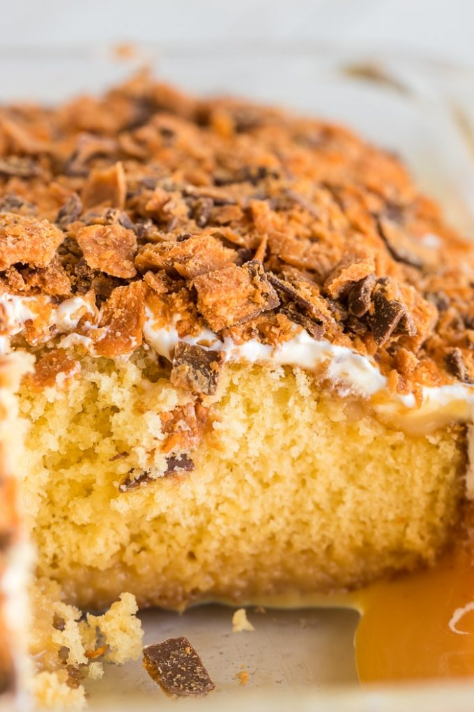 A close up of a piece of cake on a plate, with Butterfinger and Caramel