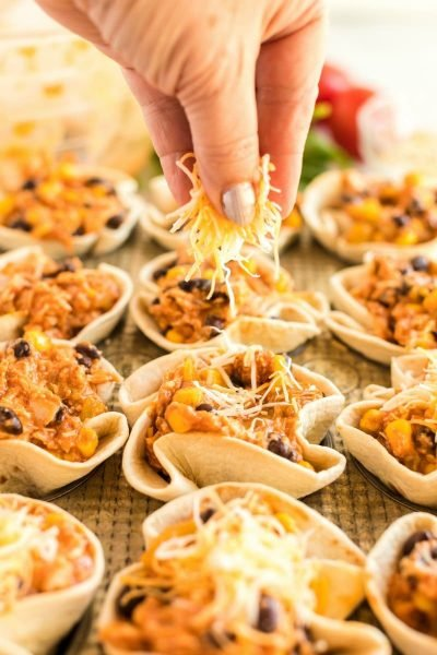 putting cheese on enchilada cups