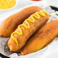 A plate with a hot dog on a bun, with Corn dog