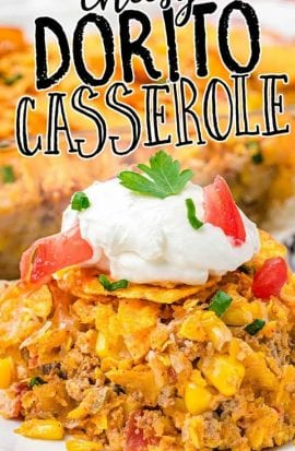 side shot of doritos casserole on a plate topped with sour cream and tomatoes