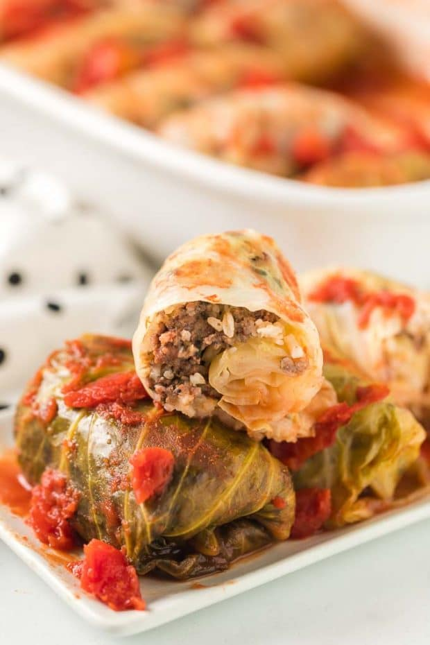 cabbage rolls on plate in front of casserole dish