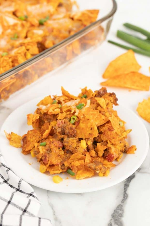 Doritos casserole on a plate in fromt of casserole dish