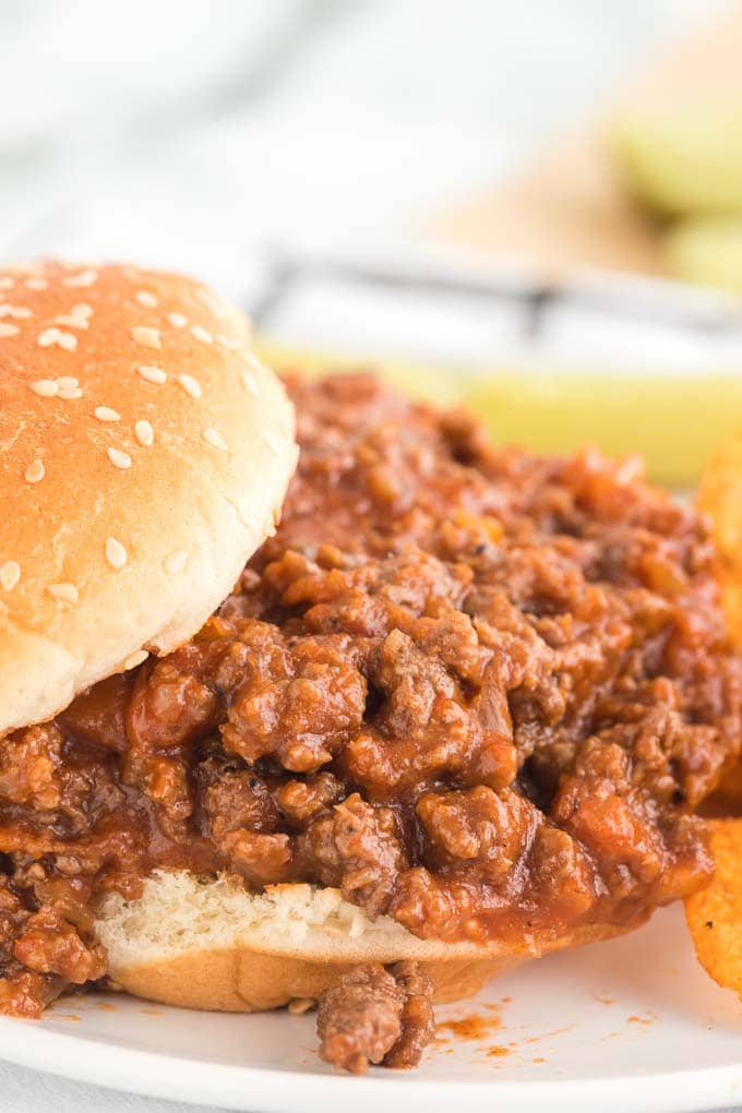 A close up of a sandwich on a plate, with Sloppy joe and Bun
